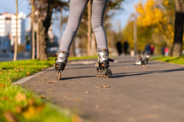 アクティブなレジャー。陽気な女の子が秋の公園でローラーブレードをしています。