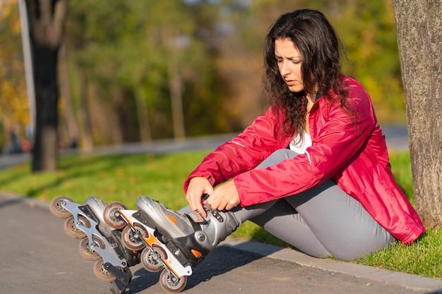 アクティブなレジャー。スポーツの女の子が秋の公園でローラーブレードをしています。