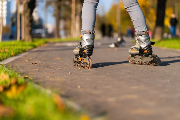 Active leisure. a sportive girl is rollerblading in an autumn park.