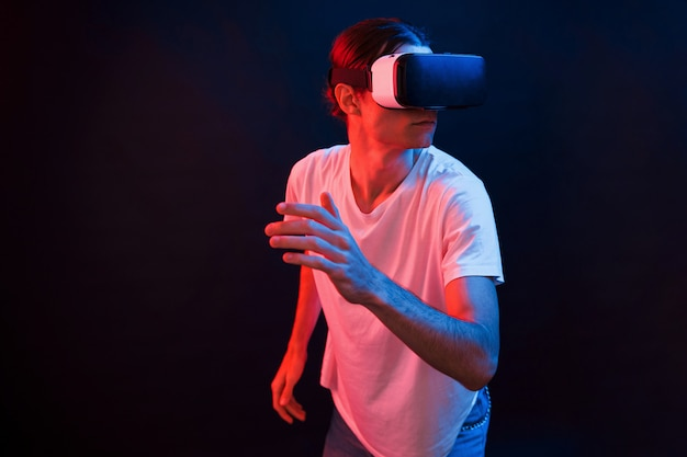 Active leisure. young man using virtual reality glasses in the dark room with neon lighting