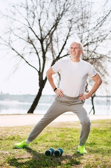 Active lifestyle. attractive mature man working out in park and smiling