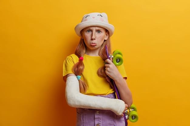활동적인 라이프 스타일, 어린 시절 및 부상 개념. 사랑스러운 주근깨가있는 어린 소녀가 페니 보드와 부러진 팔로 포즈를 취하고 스케이트 보드를 타거나 위험한 속임수를 쓰다가 부상당했습니다. 청소년 취미