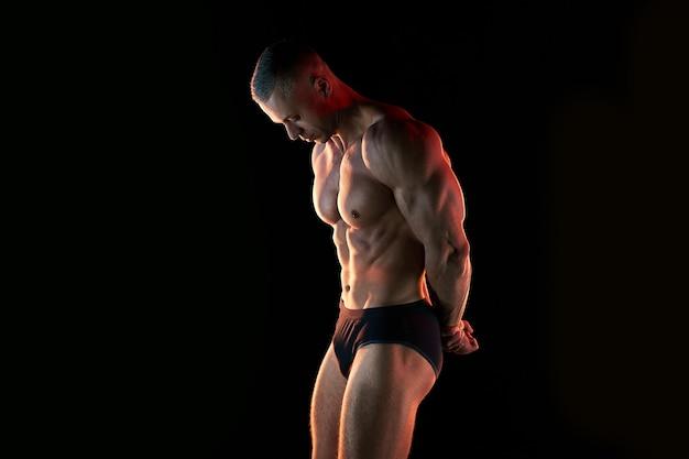 활동적인 라이프 스타일 개념. 완벽한 근육질 몸매를 보여주는 전문 보디 빌더, 배경 스포츠 및 피트니스 개념에 램프 조명