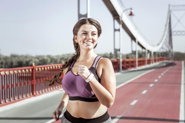 アクティブなライフスタイル。橋の上でジョギングしながら笑って喜んで素敵な女性