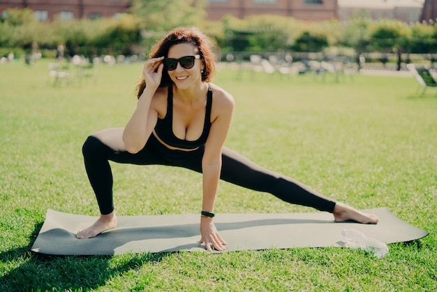 Active lifestyle and health concept. positive motivated active woman sretches on fitness mat bare feet poses outdoor dressed in activewear has smartwatch concentrated somewhere wears shades.