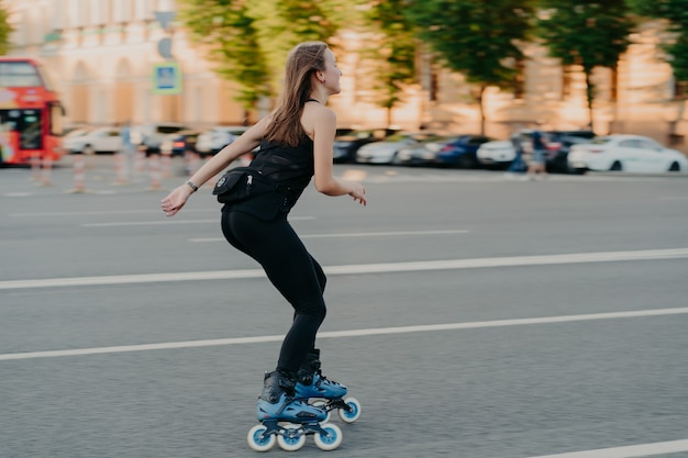 Active lifestyle and hobby concept. sporty young woman does sport outdoors rides rollerblading dressed in sportsclothes enjoys fitness activities poses in urban place on road. rollerskating.