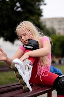 Active lifestyle in a modern city - girl puts on roller skates at the stadium