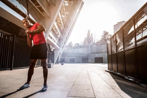 アクティブなライフスタイル。健康になりたいと思っている間トレーニングをしている素敵なよくできた男