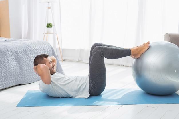 Активный образ жизни. позитивный активный человек, положив ноги на медицинский мяч, тренируясь дома