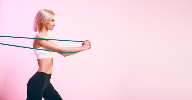흰색 상의와 검은색 레깅스를 입고 저항으로 운동하는 활동적인 라이프스타일 스포티한 아름다운 여성