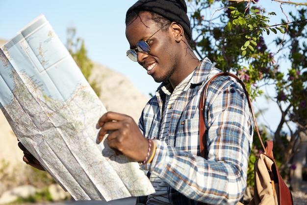 アクティブなライフスタイル、旅行、観光。自然環境の中に立っている山岳地帯での遠征に興奮したマップ感を持ってバックパックを持つ陽気なファッショナブルな若い浅黒い旅行者
