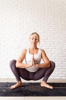 アクティブなライフスタイル。自宅でヨガを練習するスポーツウェアを着た若い魅力的な女性。屋内全長、白いレンガの壁の背景
