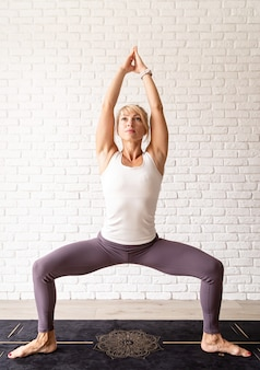 Active lifestyle. young attractive woman wearing sportswear practicing yoga at home. indoor full length, white brick wall background. t-shirt mock up