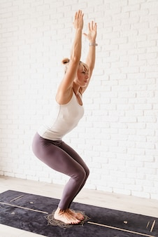 Active lifestyle. young attractive woman wearing sportswear practicing yoga at home. indoor full length, white brick wall background