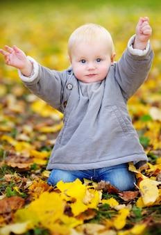 Active little baby boy in the autumn park