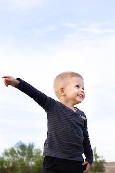 운동장에서 노는 동안 손가락을 가리키고 위를 올려다보는 활동적인 어린 소년, 흐릿한 배경에서 화려한 단풍을 가지고 밖에서 노는 유아, 야외 활동 개념