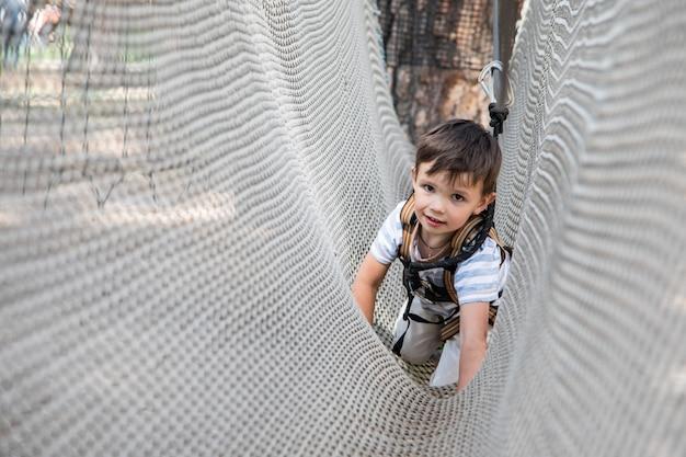 그물 등반에 활동적인 작은 아이. 아이들은 화창한 여름날에 야외에서 놀고 등산합니다.