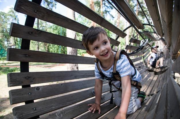 그물 등반에 활동적인 작은 아이. 아이들은 화창한 여름날에 야외에서 놀고 등산합니다. 프리미엄 사진
