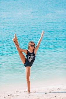 たくさんの楽しみを持っているビーチでアクティブな女の子。海岸でスポーティな運動をするかわいい子供