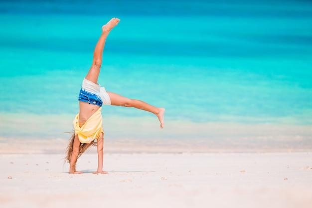 Активная маленькая девочка на пляже, весело проводящая время. милый ребенок делает спортивные упражнения на берегу моря