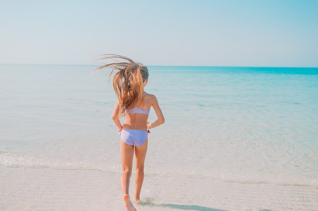 Active little girl on the beach having a lot of fun in shallow water