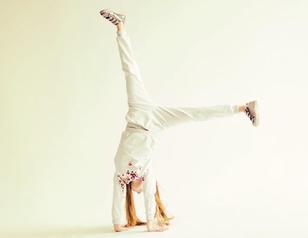 흰색 바탕에 물구나무 서기를 하 고 회색 스포츠 옷에 활성 어린 소녀