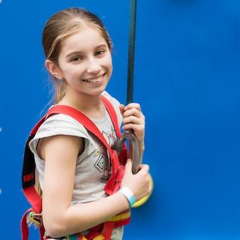 クライミングウォールの安全ハーネスでアクティブな少女