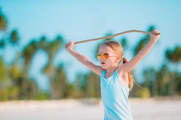 Active little girl on white beach having fun.