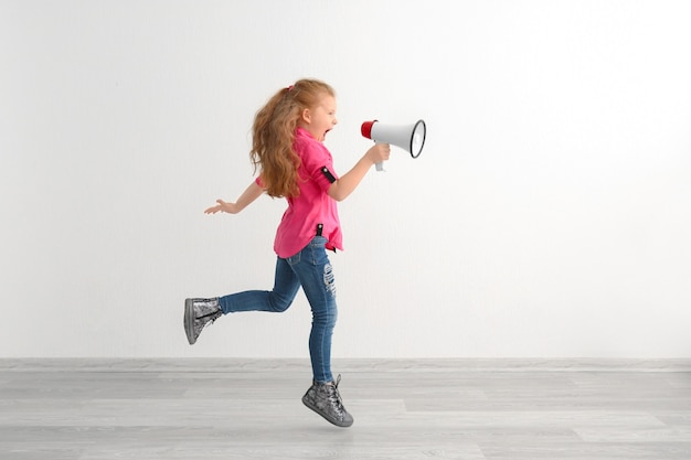 Active little girl with megaphone indoors