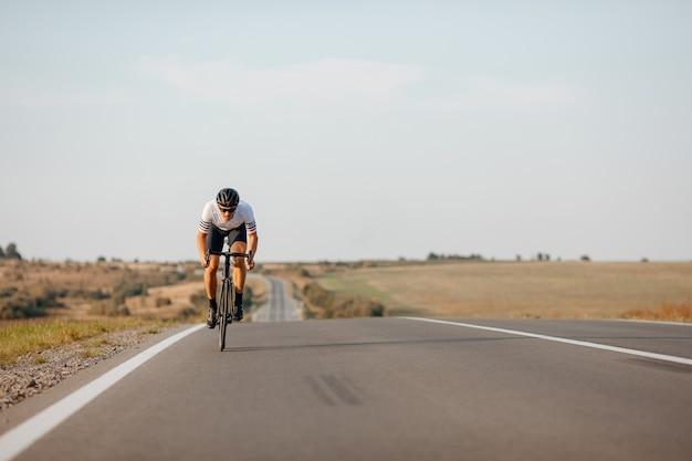 아스팔트 도로에서 자전거를 타는 동안 검은 헬멧과 안경을 쓰고 활동적인 남자 선수