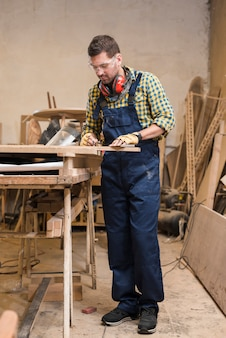 An active male carpenter measuring the wooden plank in the workshop