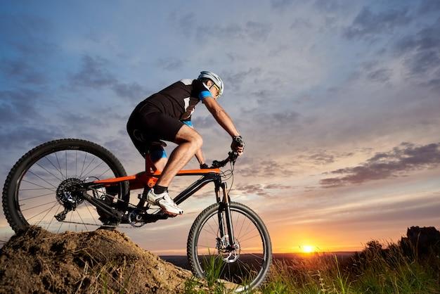 Активный мужской велосипедист, одетый в спортивную одежду и шлем, катается на велосипеде один и катится вниз по склону. спортивный и крепкий человек, катающийся на велосипеде на фоне красивого заката и розово-голубого неба вечером