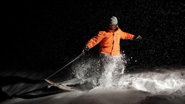 Активный мужской сноубордист в оранжевой спортивной одежде и маске прыгает на снежном холме ночью