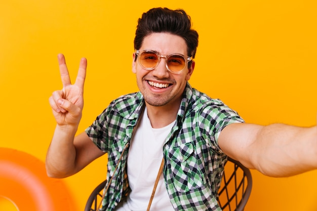 Active man in checkered outfit and glasses shows peace sign and makes selfie on isolated space.