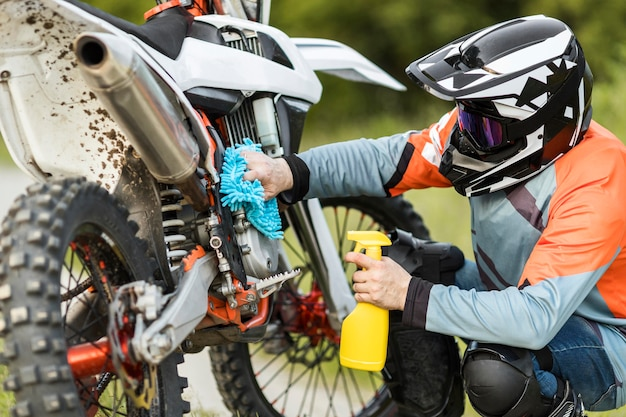Active man cleaning motorbike outdoors