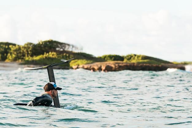 サーフィンボードにとどまる特別な機器のアクティブな男