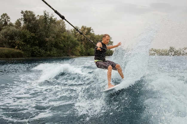 Active man riding on the wakeboard holding a rope