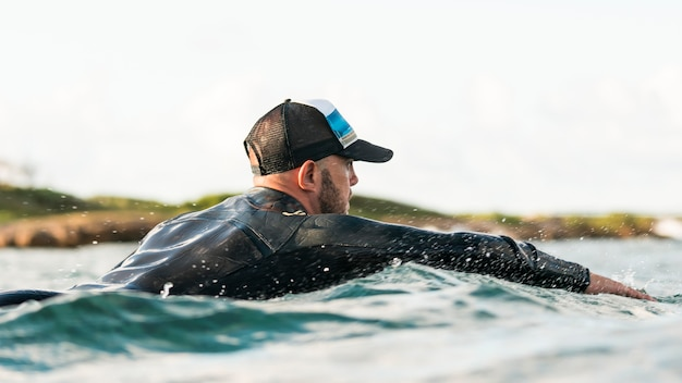 Active man in special equipment staying on a surfing board