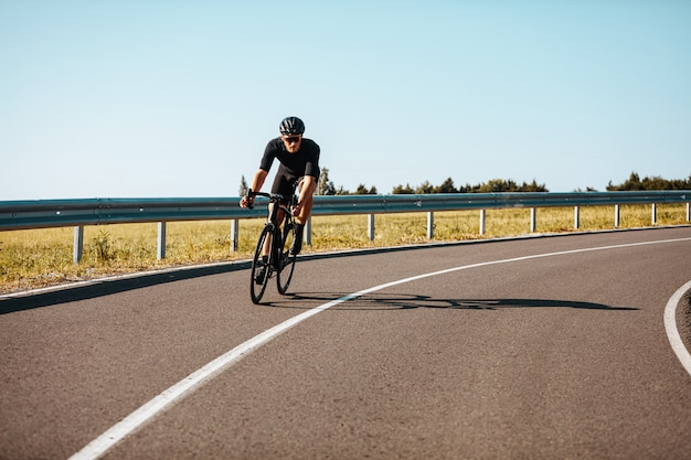 Active man in sport outfit riding bicycle on paved road