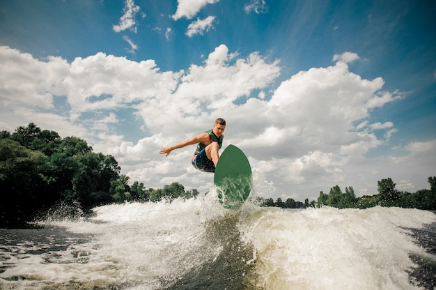 Active man wakesurfing on the board down the river against the cloudy sky and trees