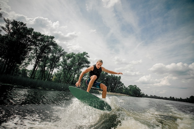 Active man wakesurfing on the board down the river