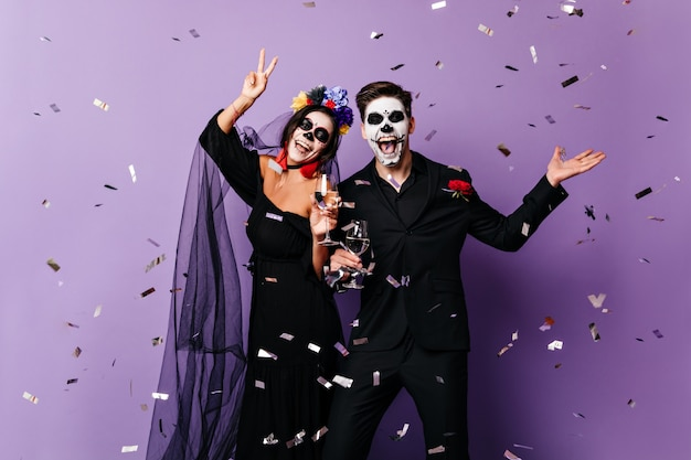 Active man and woman in costumes for halloween dance on purple background among confetti.