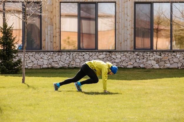 집에서 뒷마당에서 아침에 야외에서 운동하는 활성 남자 다리 운동을하는 남자
