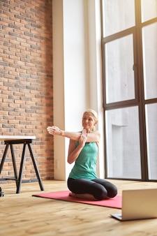 Активная зрелая блондинка улыбается, растягивая свое тело, сидя на полу во время занятий йогой