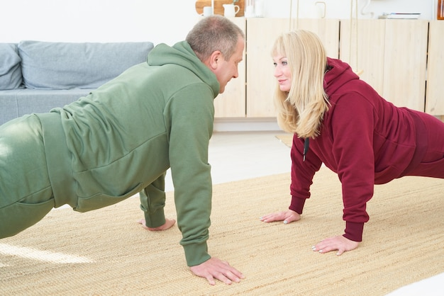 Активная зрелая пара делает упражнения на доске и смотрит друг на друга в гостиной дома.