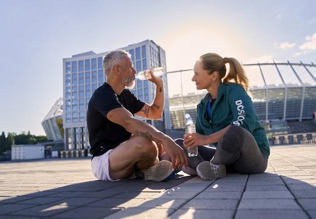Активная зрелая пара в спортивной одежде разговаривает и пьет воду, расслабляясь после тренировки на солнце