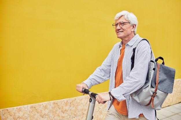 Активный зрелый мужчина катается на скутере на желтом