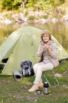 Активная зрелая женщина сидит на маленьком стуле и пьет чай в естественной среде на фоне палатки