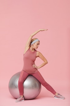 Active mature woman stretching against pink