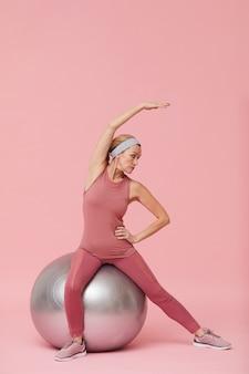 ピンクに対してストレッチアクティブな成熟した女性
